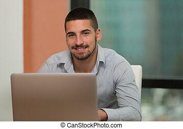 Smiling Young Student In Library Using His Laptop