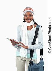 Smiling young student in winter clothes with her tablet