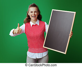 smiling young student with blackboard showing thumbs up