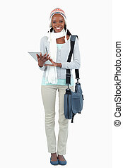 Smiling young student with scarf, hat and touchpad