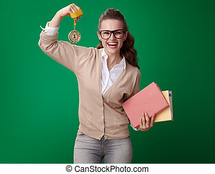 smiling young student woman with books showing medal and biceps
