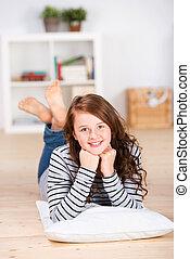 Smiling young teenage girl laying on the floor