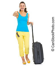 Smiling young tourist woman with wheel bag pointing in camera