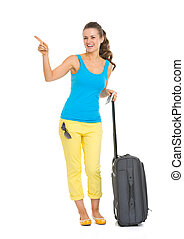 Smiling young tourist woman with wheel bag pointing on copy space
