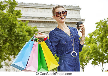 smiling young trendy woman with shopping bags in Paris, France