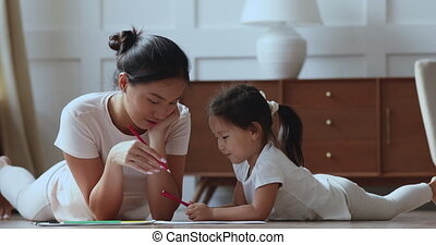 Smiling young vietnamese mother drawing pictures with cute ...
