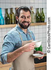 Smiling young waiter feeling good while drinking coffee at work
