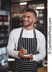 Smiling young waiter writing in notepad at coffee shop