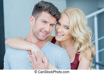 Smiling Young White Romantic Couple Looking at Camera.