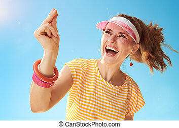 smiling young woman against blue sky fingers snapping