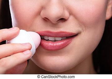 Young Woman Applying Balm On Her Lips
