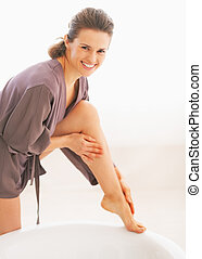 Smiling young woman applying cream on leg in bathroom