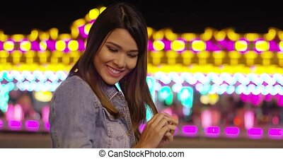 Smiling young woman at a colorful fairground standing in...