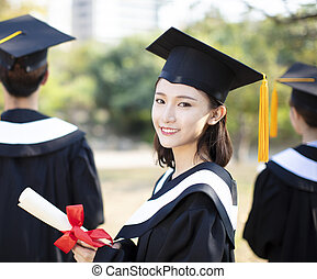smiling young woman at graduation showing her diploma