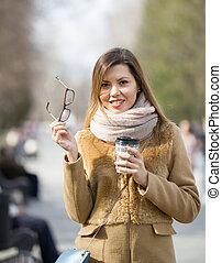 Smiling young woman at park hold in hands glasses and coffee