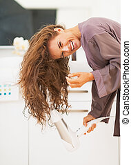 Smiling young woman blow drying hair in bathroom