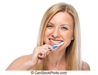 Smiling young woman brushing teeth