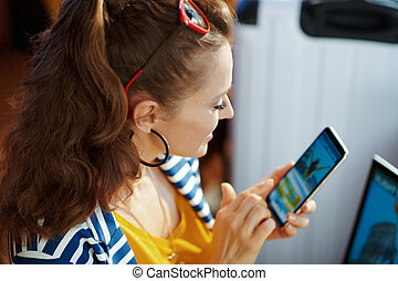 smiling young woman buying flights online on smartphone