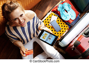 smiling young woman buying tickets online on tablet PC