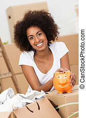Smiling young woman caressing her piggy bank