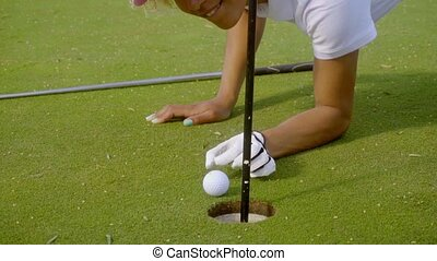 Smiling young woman cheating at golf preparing to flick her ...