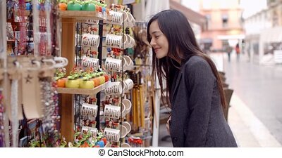 Smiling young woman checking out shop merchandise - Happy...