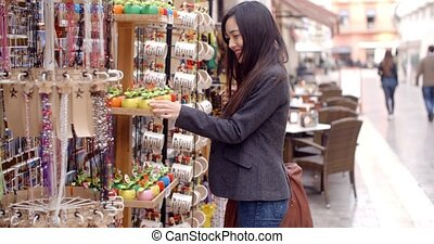 Smiling young woman checking out shop merchandise