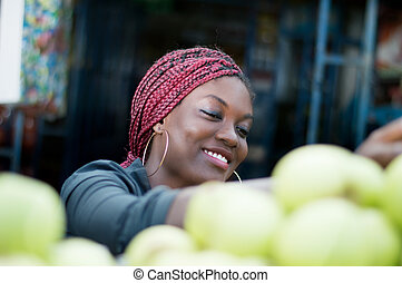 smiling young woman choosing apple  at street market.