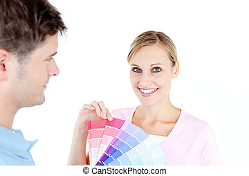 Smiling young woman choosing colors for painting a room