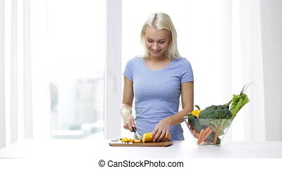 smiling young woman chopping squash at home