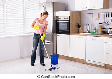 Young Woman Cleaning Kitchen Floor With Mop
