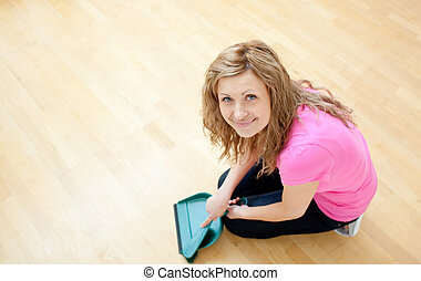 Smiling young woman cleaning the floor