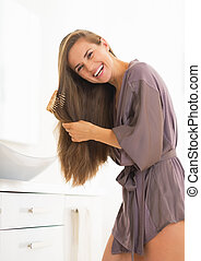 Smiling young woman combing hair in bathroom