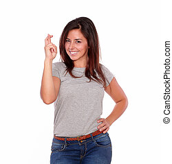 Smiling young woman crossing her fingers for luck