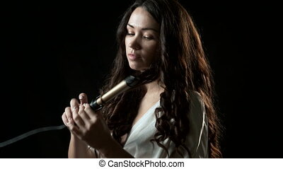 Smiling young woman curling her long brown hair with curler....