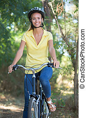 smiling young woman cycling in the forest