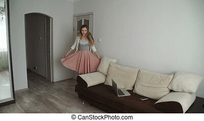 Smiling young woman Dances and falls on the sofa, fools around, spoils, lying on the sofa at home, she is relaxing and hugging a soft pillow