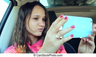 Smiling young woman dancing and taking selfie picture with smart phone camera in the car. 3840x2160