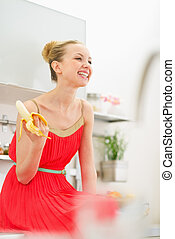 Smiling young woman eating banana in kitchen