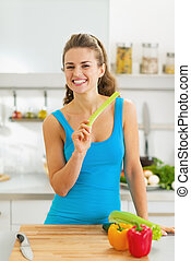 Smiling young woman eating celery in modern kitchen