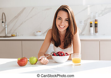 Smiling young woman eating fresh berries from a bowl while...