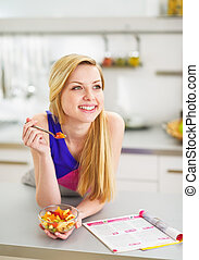 Smiling young woman eating fruits salad in kitchen