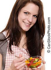 smiling young woman eating mixed salad