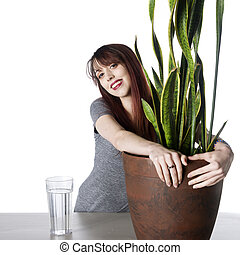 Smiling Young Woman Embracing Green Plant in a Pot