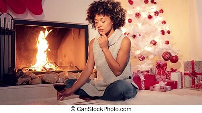 Smiling young woman enjoying a book at Christmas