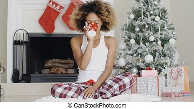Smiling young woman enjoying a cup of Xmas coffee
