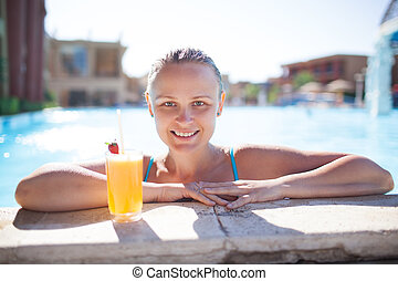 Smiling young woman enjoying a drink in the pool
