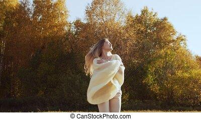 Smiling young woman enjoying nature in autumn season.