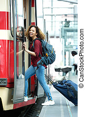 Smiling young woman entering train