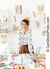 Smiling young woman fashion designer standing at her workplace